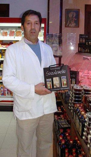Antonio posa en el supermercado familiar con una caja de licores. LA VOZ