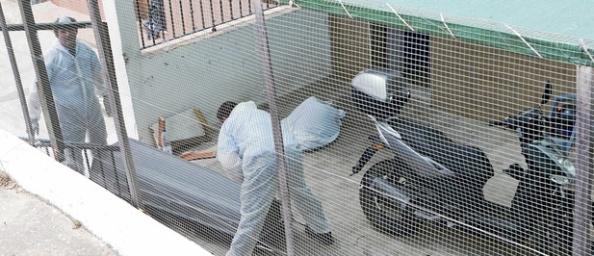 Dos operarios retiran los restos en la vivienda.  - Foto: Efe