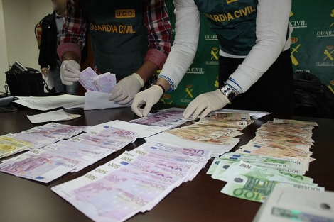 Los agentes hacen recuento de los billetes descubiertos.